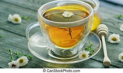 Closeup of cup with camomile tea - Closeup shot of glass mug...