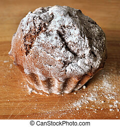 closeup of cupcake with powdered shugar on the wood background