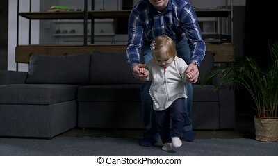Closeup of cute toddler girl making steps at home