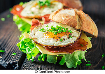 Closeup of delicious burger with lettuce, bacon and eggs