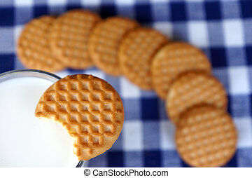 Closeup of dipping a cookie in milk