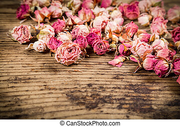 Closeup of dried roses on wooden background