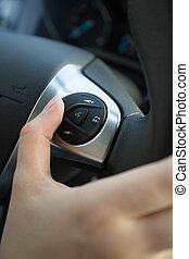 Closeup of driver using control panel on steering wheel