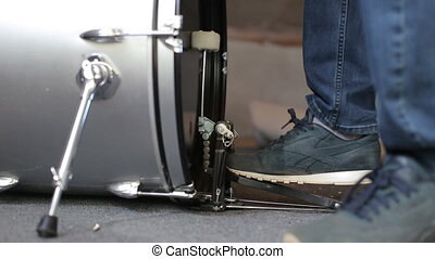 Closeup of drummer's foot moving drum bass pedal.