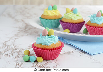 easter cupcakes on a platter with eggs
