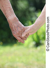 Closeup of elderly couple holding hands