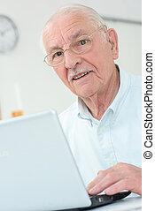 Closeup of elderly gentleman using laptop