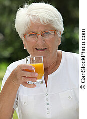Closeup of elderly woman drinking fruit juice from a glass