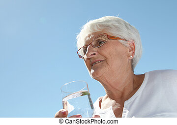 Closeup of elderly woman drinking water from a glass