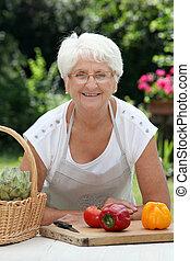 Closeup of elderly woman in garden with basket of fresh vegetables