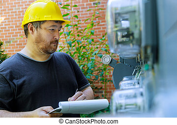 Closeup of electrical engineer in yellow helmet technician writing on clipboard in front fuse box