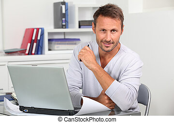 Closeup of employee in the office working on laptop computer