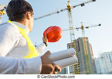 Closeup of engineer posing on building site with orange ...