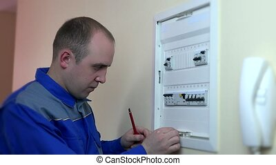 Closeup of experienced electrician repairing circuit breaker...