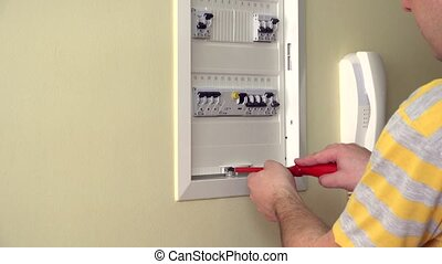 Closeup of experienced man repairing circuit breaker. -...
