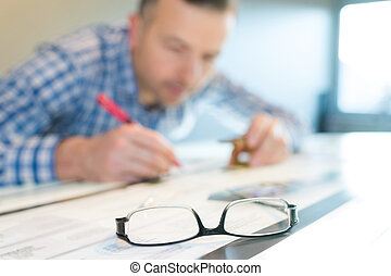 closeup of eyeglasses on table man working in background