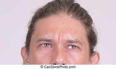 Closeup of eyes of man thinking against white background -...