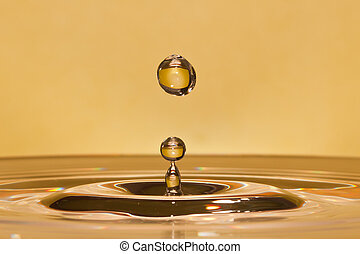 Closeup of falling water-drop in a yellow liquid