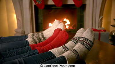Closeup of family feet in woolen socks warming by the fireplace decorated for Christmas