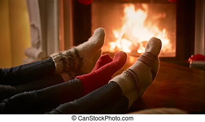 Closeup of family in woolen socks warming by the burning fireplace at house