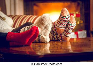 Closeup of family warming feet at fireplace