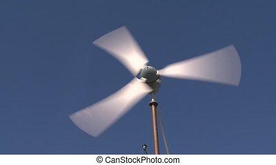Closeup of fast spinning wind turbine propeller on blue sky...