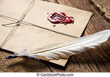 Closeup of feather on envelope with red sealant and inkwell