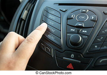 Closeup of female finger pressing radio button on car control panel