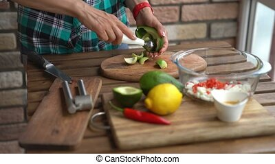 Closeup of female hands cutting avocado for guacamole at...