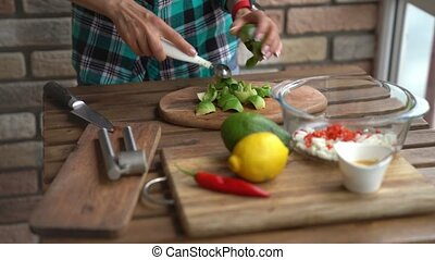 Closeup of female hands cutting avocado for guacamole at table in home kitchen