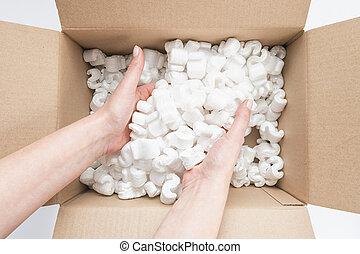 Closeup of female hands digging in a heap of packing peanuts in a Box