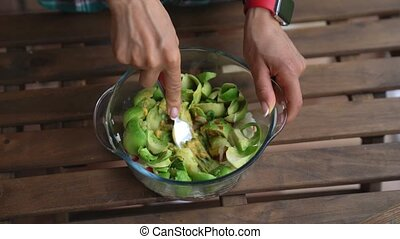 Closeup of female hands mixing products for guacamole at...