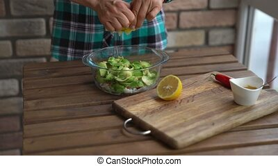Closeup of female hands squeezing half a lemon to avocado...