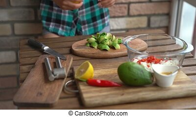 Closeup of female hands squeezing half a lemon to avocado for guacamole at table in home kitchen