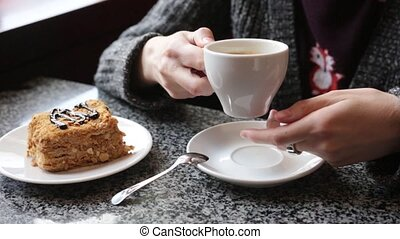 Closeup of female hands with a cup of coffee.