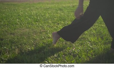 Closeup of female legs, business woman in black pants having fun barefoot on a lawn, freedom.