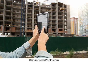 Closeup of female realtor using digital tablet at building under construction