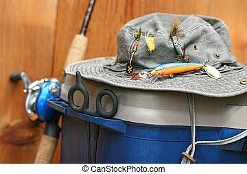 Fishing tackle box, hat and reel on wood