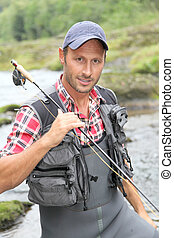 Closeup of fly-fisherman holding fishing rod in river