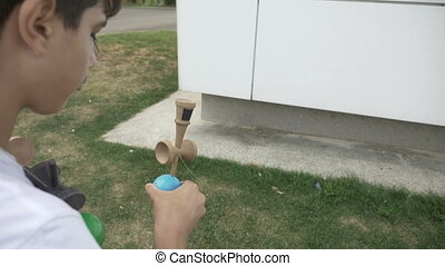 Closeup of focused kid balancing kendama ball on spike in...