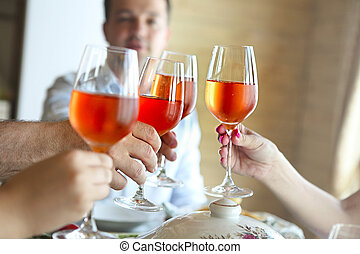 Closeup of four glasses with rose wine being clinked together