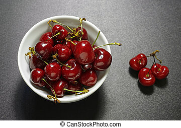 closeup of fresh cherries in a white bowl on grey background