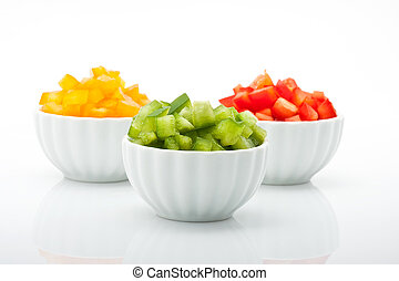 fresh green, yellow and red peppers in bowl isolated on white background