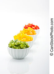 fresh green, yellow, orange and red peppers in bowl isolated on white background