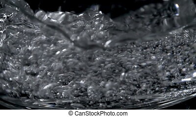Closeup of fresh mineral water falling in glass on black...