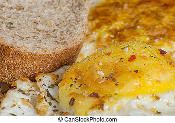 Closeup of fried eggs and bread with seasoning. Delicious and healthy breakfast.