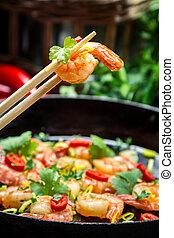 Closeup of fried shrimp on chopsticks