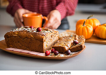 Closeup of fruit and seed loaf with woman's hands holding mug