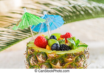 Closeup of fruits salad in pineapple with cocktail umbrellas