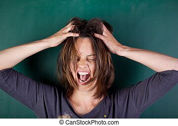 Closeup of frustrated woman with hands in hair screaming against chalkboard